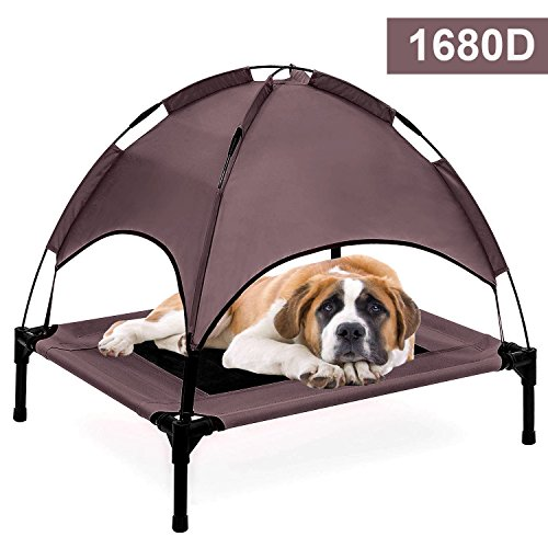 A dog resting on a pet cot with canopy.