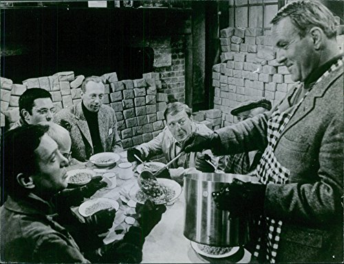 Vintage photo of Man serving food to a group of men.