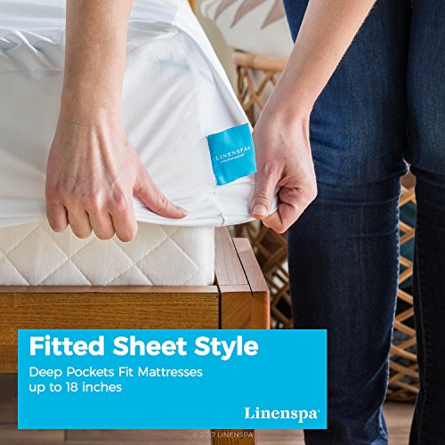 man in dark blue jeans fitting a Linenspa Premium Smooth Fabric Mattress Protector on a mattress in a wooden bed