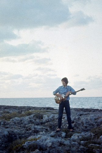 George Harrison Poster - George Harrison in Help! iconic image playing guitar on Bahamas beach The Beatles movie 24x36 Poster
