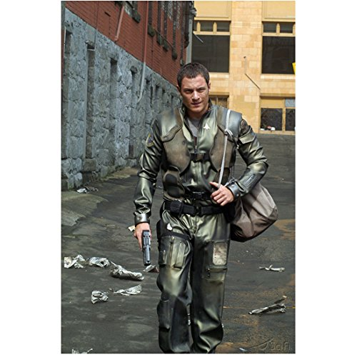 (Tahmoh Penikett as Capt. Karl Agathon carrying gun and bag walking down street 8 x 10 Inch Photo)