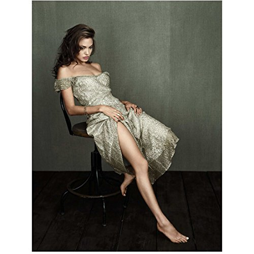Angelina Jolie Wearing Printed Dress Off Shoulder Sitting Leaning Back in Chair One Leg Out Hands Holding Dress Looking Down 8 X 10 Inch Photo