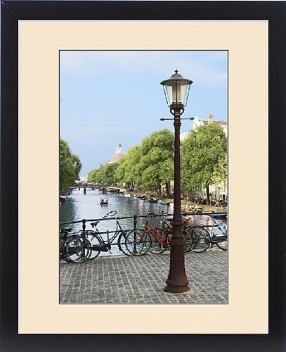 Framed Print of Amsterdam, Holland, Old gas lamp post and bicycles on a bridge over a canal in by Fine Art Storehouse