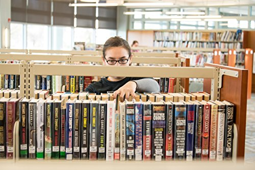 A military family member dusts the book stacks in the library at the Armed Forces Retirement Home in