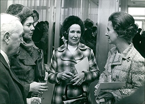 (Vintage photo of Queen Fabiola of Belgium and Queen Paola of Belgium communicating with a man and woman.)