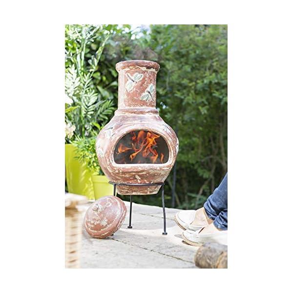 Adding wood to a lit La Hacienda Alegria Clay Chimenea Medium Terracotta and Blue burning wood
