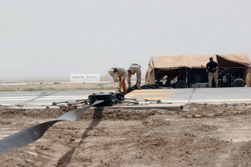 Photo US Air Force (USAF) personnel from the 407th Expeditionary Civil Engineer Squadron (ECES) install a Mobile Aircraft Arresting System (MAAS) which consists of two identical units with one installed on each side of the runway, the system uses a special nylon tape as the drive member, 05/24/2004