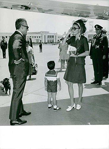 Vintage photo of Mohammad Reza and Farah Pahlavi standing with son Alireza under aeroplane wing.