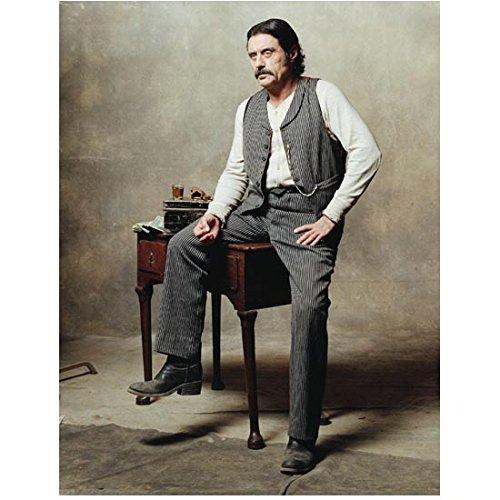 Deadwood Ian McShane as Al Swearengen one leg up resting on desk 8 x 10 Inch photo