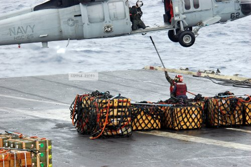 Photo A U.S. Navy Aviation Ordnanceman hooks ammunition to a MH-60S Knight Hawk helicopter from Helicopter Sea Combat Support Squadron 25, during a vertical replenishment between the Aircraft Carrier USS KITTY HAWK (CV 63) and the Military Sealift Command Kilauea Ammunition Ship USNS FLINT (T-AE32) in the Philippine Sea, Dec. 8, 2006. (Navy photo by Mass Communication SPECIALIST SEAMAN Kyle D. Gahlau) (Released), 12/08/2006