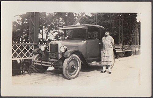 Elderly woman standing beside Chevrolet Coupe on iron bridge snapshot 1927 NY