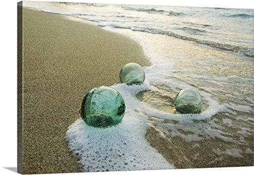 Mary Van de Ven Premium Thick-Wrap Canvas Wall Art Print entitled Three Glass Fishing Floats Roll On The Sandy Shoreline With Ripples Of Water And Seafoam -  Canvas On Demand, 1405284_24_24x16_none