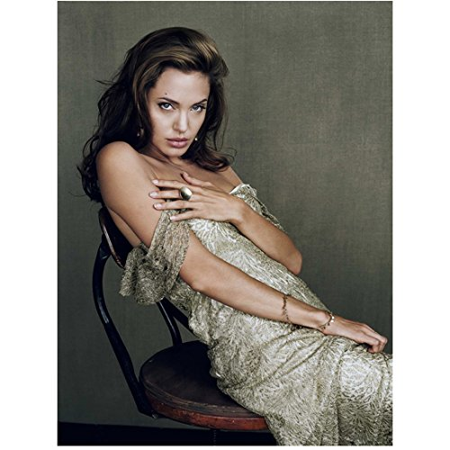 Angelina Jolie Wearing Printed Dress Falling Off Shoulder Sitting Leaning Back in Chair Hand on Chest Head Tilted Down Looking Forward 8 X 10 Inch Photo