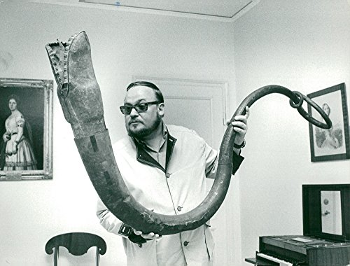 """Vintage photo of Music Museum. The artist Yngve Gamlin with an old musical instrument called """"m246;gla""""."""
