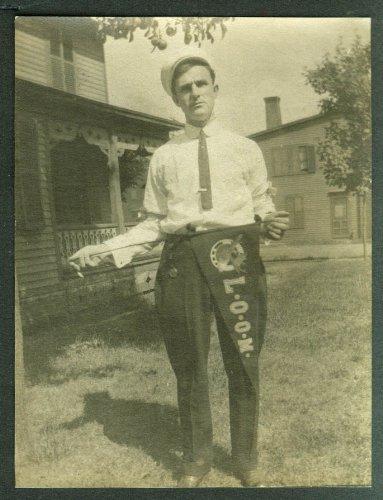 Man in cap & short necktie holds LOOM Moose pennant snapshot ca 1920s