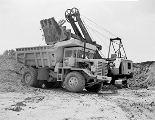 Earth mover putting soil on dump truck Poster Print