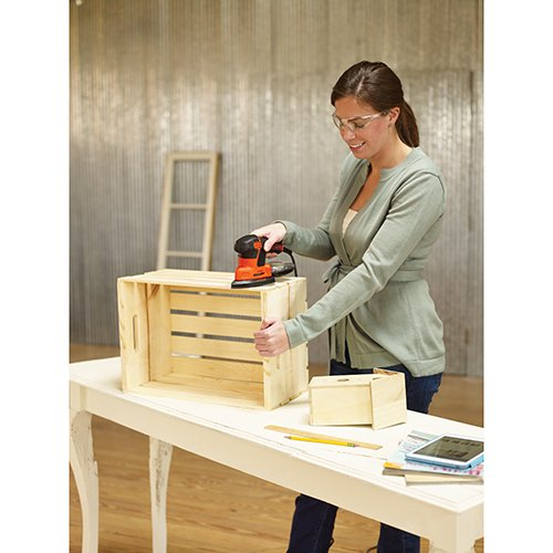Woman wearing safety goggles and polishing the side of a wooden crate with a detail sander.