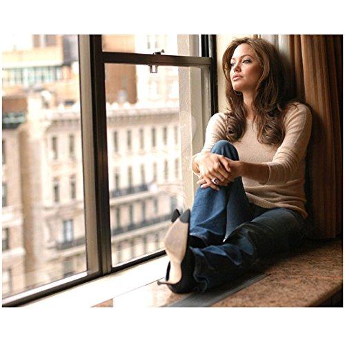 Angelina Heels - Angelina Jolie Wearing Jeans Long Sleeve Tan Top Heels Sitting on Windowsill Arms Around One Bent Leg Looking Out Window 8 X 10 Inch Photo