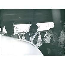 Vintage photo of Nahashon Isaac Njenga Njoroge seated in between two police officers inside the prison van. 1969.