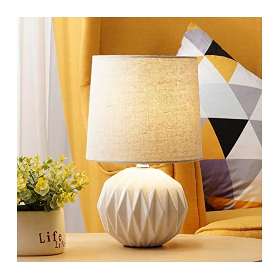 "Tayanuc Small Geometric Ceramic Bedside Nightstand Table Lamp, White Textured Desk Lamp Linen Drum Fabric Shade for Living Room Family Bedroom - Ceramic Table Lamp: This white ceramic table lamp shaped like a pineapple takes a fresh twist with textural geometric ceramic body. The solid color allows the plentiful texture and modern silhouette to truly shine and adds a hint of glam to nightstand. Excellent gifts for the coming Thanksgiving Day. Materials: The inimitable desk lamp will turn heads with its smooth textured curves balanced on a white ceramic base. It is paired with beige linen drum fabric shade that casts an ambient glow. Dimensions: 7.5"" D x 12.6"" H. - lamps, bedroom-decor, bedroom - 51weus0mgFL. SS570  -"