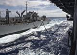 The amphibious assault ship USS Peleliu (LHA 5), right, receives fuel and supplies during a replenis