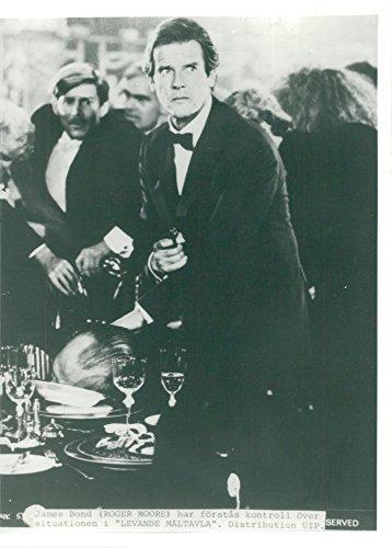 Vintage photo of Roger Moore as James Bond in Live Scoreboard. - Scoreboard Photo