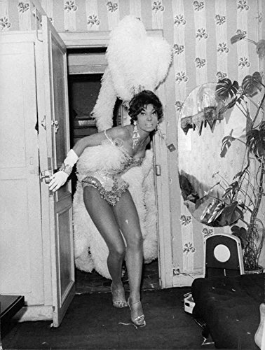 vintage-photo-of-yvonne-menard-in-a-costume-striking-a-pose-at-the-open-door-in-folies-bergere-1960