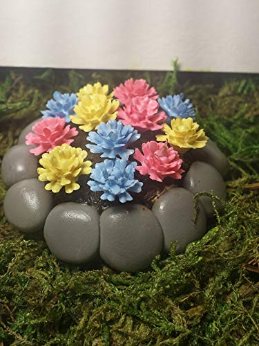 Fairy garden miniature flower bed. Pink, blue, and yellow flowers in stone look flower bed. ()