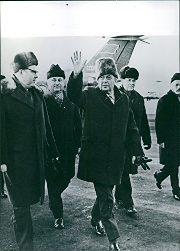 Vintage photo of British Prime Minister Harold Wilson wearing a trim fur hat, waving cheerily to crowds at Moscow airport during his visit to the Soviet Union in February 1975. He is escorted by Soviet - Wilson Port