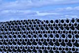 Looking over a stack of pipes which are used in construction industry. Iceland 30x40 photo reprint
