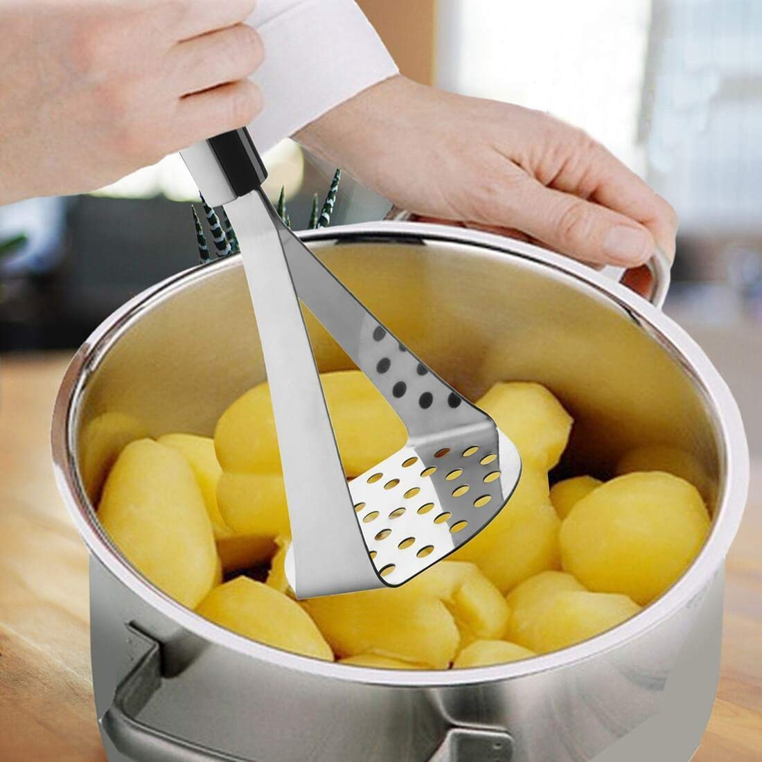 A potato masher is used to mash potatoes in the image.
