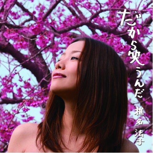 赤い花の下で空を見つめて微笑む椎名法子