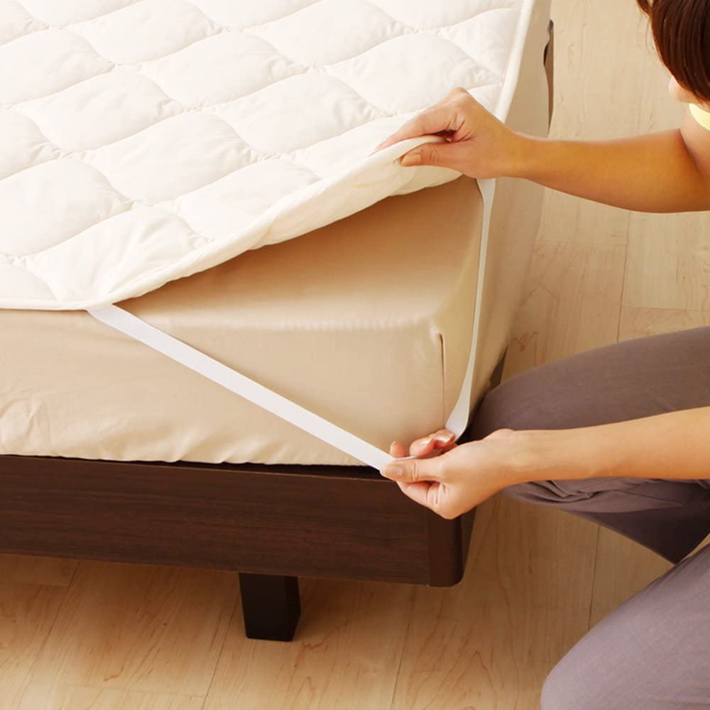 ベッドパッドを敷く女性