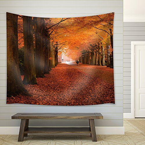 Man Walking on a Road Leading to a Forest During Fall Time Fabric Tapestry