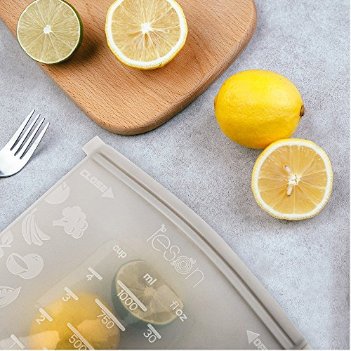 Airtight silicone bag beside a fork and a whole and slices of lemons on a wood chopping board.