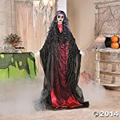 Let Madame Misery greet your trick-or-treaters in spooky style this Halloween. This ghastly animated Halloween decoration features flashing red eyes and tattered fabric clothing for the perfect addition to your haunted house. With her black lace veil...