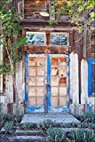 Fine art photograph of a well worn wooden blue door with reflecting window panes at distressed abandoned garden home in a New Mexico ghost town.