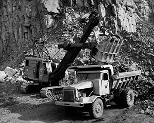 Earth mover loading rocks in to a dump truck Poster Print