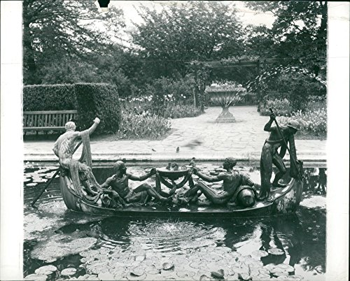 Vintage photo of A secluded corner of the flower garden with its lily pond and an unusual fountain shaped like a boat.