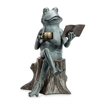 metal frog reading book on log