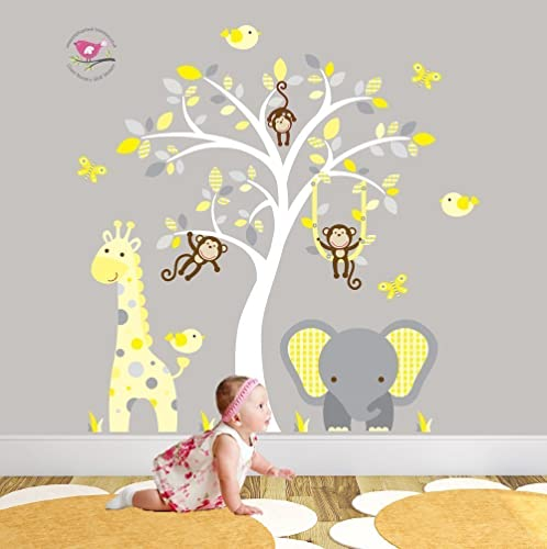 Jungle nursery wall art featuring a giraffe elephant and monkeys around a white tree mural