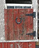 Boarded Barn Window with Horseshoe. Photograph of an old barn window is boarded shut by a handmade red plank shutter with an old iron horse shoe. It has just started snowing.