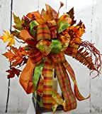 Looking for the perfect decor piece for the Fall? This is it!! This beautiful swag features 6 different wired fall ribbons in a full bow and is accented with a large pumpkin, sprays of fall leaves, flowers, and other fall foliage accents This...