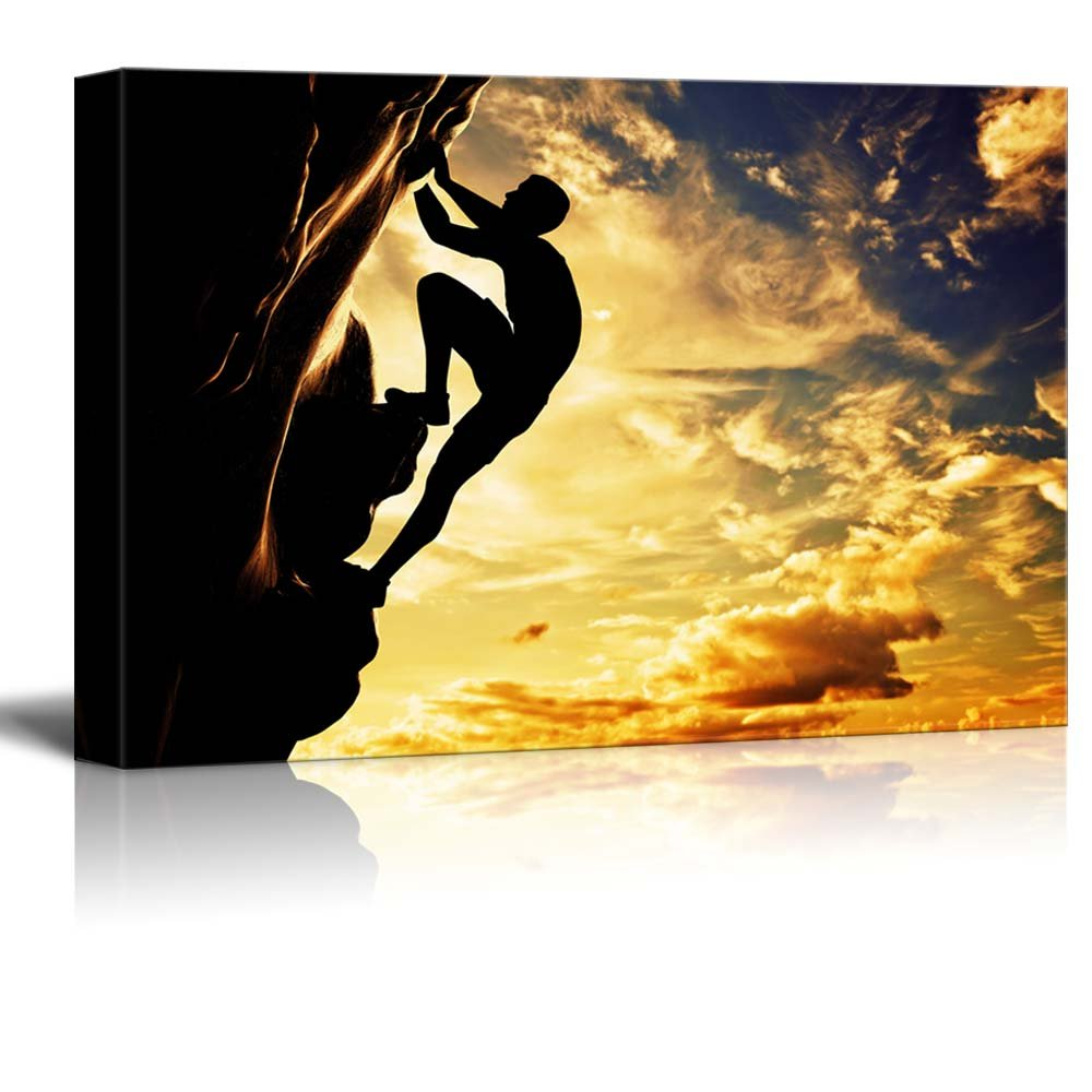 A Silhouette of a Man Climbing on Rock Mountain Cliff at Sunset ...