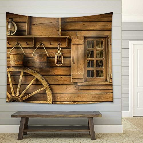 Detail of Old Wagon Wheel Next to a Wooden Wild West Typical House Fabric Wall