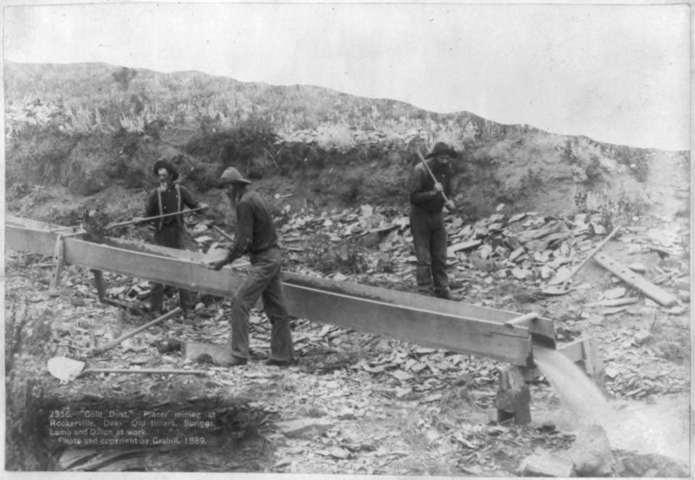 Dak John C Lamb and Dillon at work Grabill photographer. Placer mining at Rockerville Gold Dust photograph: Three men placer mining with shovels H. Old timers picks and pan Spriggs