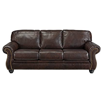 Ashley Furniture Signature Design   Bristan Traditional Style Faux Leather  Sofa With Nailhead Trim   Walnut