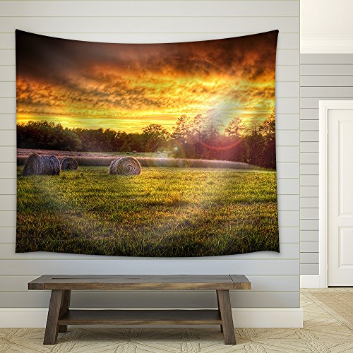 Beautiful Sunset Lighting a Field with Hay Rounds Producing Brilliant and Amazing Colors Fabric Wall Tapestry