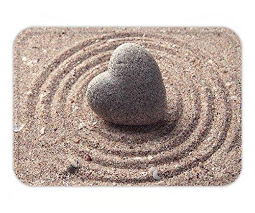 Mexican Sand Shape (Beshowere Doormat grey zen stone in shape of heart on sand background)