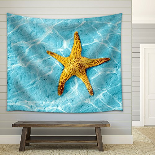 Starfish in blue water with light reflection Fabric Wall